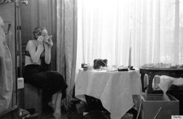 In 1953, a model does her own make-up before a fashion show